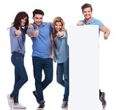 Casual friends presenting a blank board and making the ok sign. Group of casual friends presenting a blank board and making the ok thumbs up hand sign on white Stock Photo