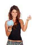 Casual girl with a blue piggy-bank. Isolated on a white background stock images