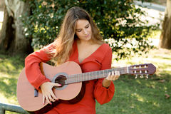 Casual girl dressed in red playing guitar Royalty Free Stock Images