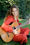 Casual girl dressed in red playing guitar Royalty Free Stock Photography