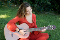 Casual girl dressed in red playing guitar Stock Photo