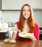Casual  girl eating jacket potatoes Royalty Free Stock Photography
