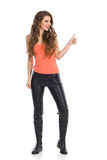 Casual Girl Giving Thumb Up. Smiling young woman in black leather trousers, orange shirt and boots standing, looking away and showing thumb up. Full length Stock Images
