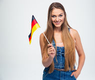 Casual girl holding Germany flag. Portrait of a casual young girl holding Germany flag isolated on a white background. Looking at camera Royalty Free Stock Image