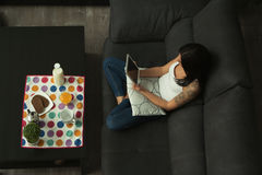 Casual girl at home taking the breakfast and reading the tablet Royalty Free Stock Image