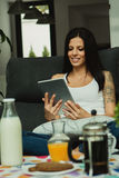 Casual girl at home taking the breakfast and reading the tablet Stock Photography