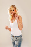 Casual girl in jeans eating a bar of chocolate. Casual pretty blonde girl in jeans and t-shirt smiling and eating a bar of chocolate stock photo