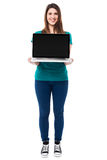 Casual girl presenting brand new laptop Royalty Free Stock Photography