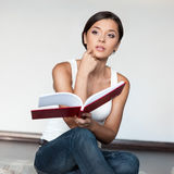Casual girl sitting with book Stock Photography