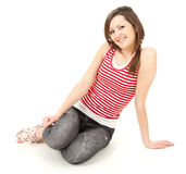 Casual girl sitting on the floor, full length Stock Image