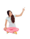 Casual girl sitting on the floor pointing something Royalty Free Stock Image