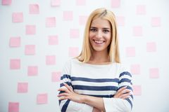 Casual girl standing with arms folded in office Stock Image
