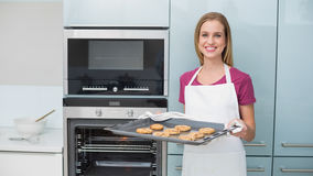Casual gleeful woman holding baking tray with cookies Royalty Free Stock Photo
