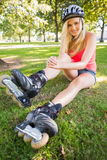Casual gorgeous blonde wearing roller blades and helmet Stock Image