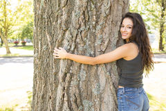 Casual gorgeous brunette embracing a tree looking at camera Royalty Free Stock Images