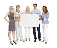 Casual group of people holding a billboard. Casual group of people holding a blank billboard on white background stock photo