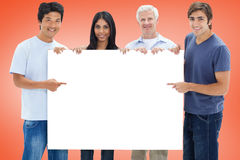 Casual group showing white card Royalty Free Stock Image