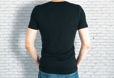 Casual guy in black shirt back. Back view of casual guy in blank black shirt on brick background. Retail concept. Mock up Royalty Free Stock Photo