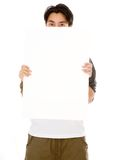 Casual guy hiding behind a white board Royalty Free Stock Image