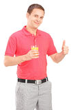 Casual guy holding a juice and giving thumb up Royalty Free Stock Image