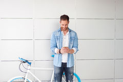 Casual guy next to a vintage bicycle with the mobile Stock Photography