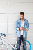 Casual guy next to a vintage bicycle with the mobile Royalty Free Stock Photos