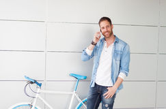 Casual guy next to a vintage bicycle with the mobile Stock Photo