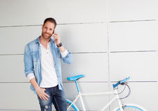 Casual guy next to a vintage bicycle with the mobile Royalty Free Stock Image
