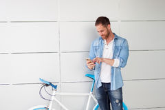 Casual guy next to a vintage bicycle with the mobile Royalty Free Stock Photo
