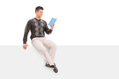 Casual guy reading a book seated on a blank panel Royalty Free Stock Photos