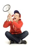 Casual guy shouting through megaphone. Young man over white background Royalty Free Stock Photography