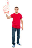 Casual guy showing large pointy boo hurray hand. Toy. Full length portrait stock photos