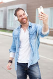 Casual guy in the street listening music with his mobile. Casual guy with a denim clothes in the street listening music with his mobile Stock Photography
