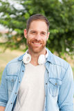 Casual guy with white headphones is taking a walk. In the park in his free time Stock Photos