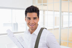 Casual handsome architect smiling at camera holding blueprint Stock Photography