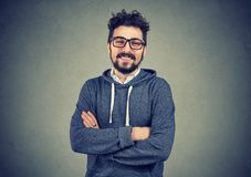 Casual handsome man smiling at camera. Young hipster man with beard wearing glasses and smiling at camera standing with hands crossed Stock Photo