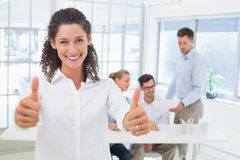 Casual happy businesswoman showing thumbs up to camera Royalty Free Stock Photography