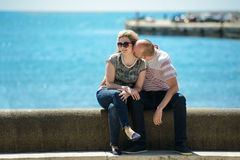 Casual happy couple dating and hugging sitting outdoor at the beach Stock Images