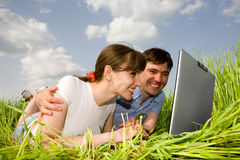 Casual happy couple on a laptop computer. Outdoors. Lay on the green grass Royalty Free Stock Images