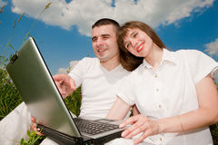 Casual happy couple on a laptop computer. Outdoors smiling under blue sky Stock Image