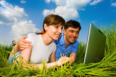 Casual happy couple on a laptop computer outdoors. royalty free stock photography