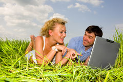 Casual happy couple on a laptop computer outdoors. Lay on the green grass Stock Image