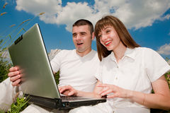 Casual happy couple on a laptop computer outdoors. Smiling under blue sky Royalty Free Stock Image