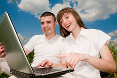 Casual happy couple on a laptop computer outdoors. Smiling under blue sky Royalty Free Stock Images