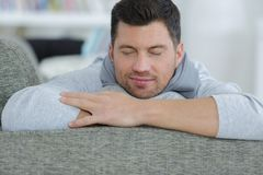 Casual happy man relaxing on couch in bright living room royalty free stock photos