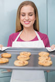 Casual happy woman looking at baking tray with cookies. In bright kitchen royalty free stock images