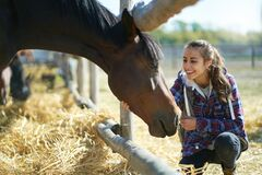 Casual happy woman petting horse on countryside farm or ranch