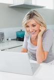 Casual happy woman using laptop in kitchen Stock Image