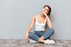Casual happy wondering woman sitting on the floor Royalty Free Stock Images