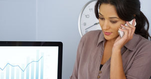 Casual Hispanic business woman talking on mobile phone in office Stock Images